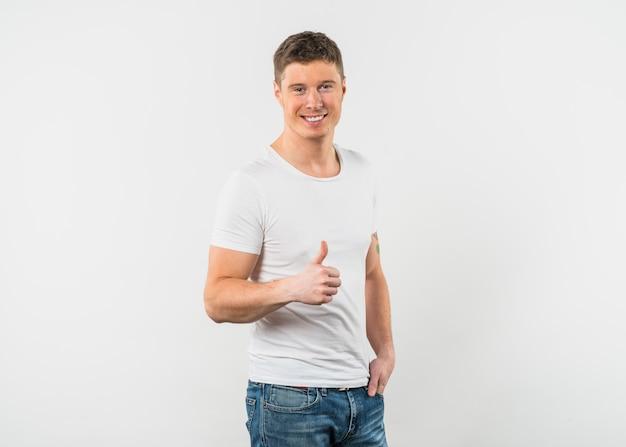 De glimlachende jonge mens die duim toont ondertekent omhoog tegen witte achtergrond