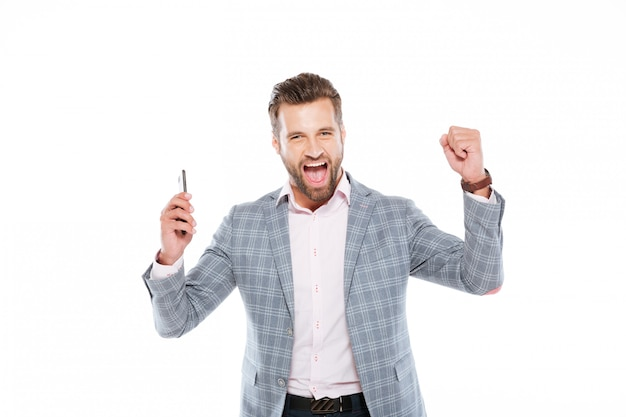 De glimlachende jonge mens die mobiele telefoon met behulp van maakt winnaargebaar.