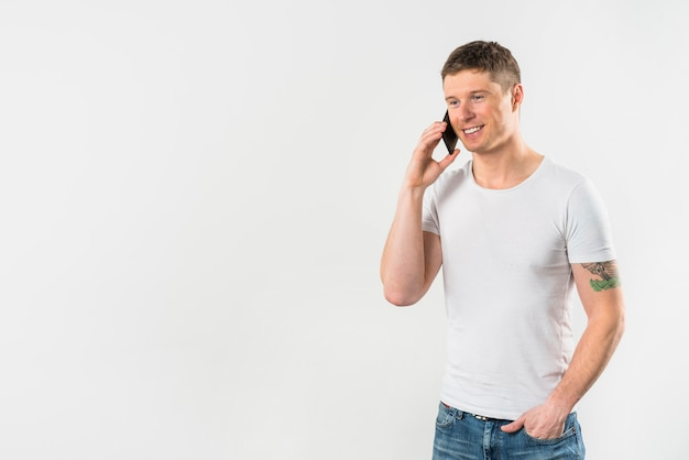 De glimlachende jonge mens die op mobiele telefoon met van hem spreken dient zak in
