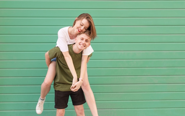 De glimlachende jonge mens die vrijetijdskleding draagt, draagt een gelukkig meisje op zijn rug