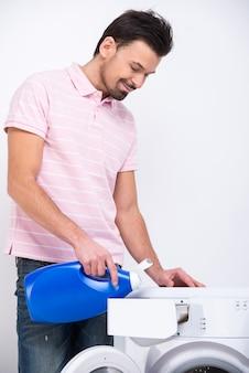 De glimlachende jonge mens doet wasserij met wasmachine.