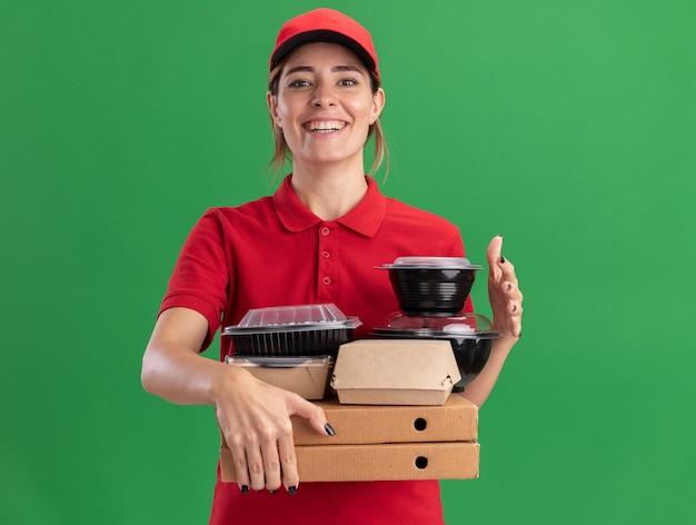 De glimlachende jonge mooie bezorger in uniform houdt papieren voedselpakketten en containers op pizzadozen die op groene muur worden geïsoleerd