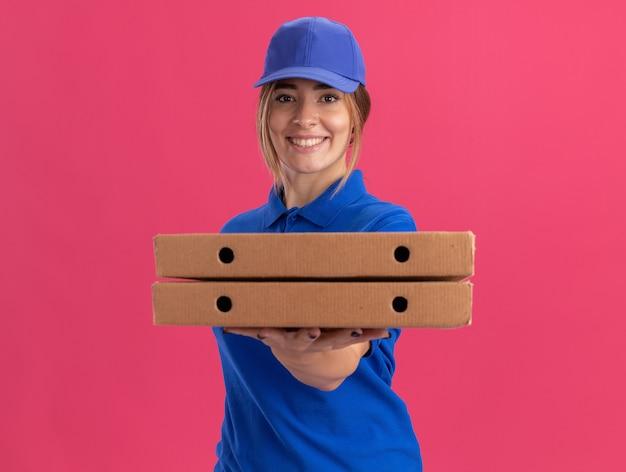 De glimlachende jonge mooie bezorger in uniform houdt pizzadozen en kijkt naar voorzijde geïsoleerd op roze muur