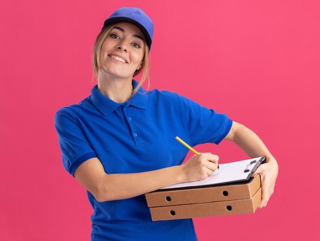 De glimlachende jonge mooie bezorger in uniform houdt pizzadozen en schrijft op klembord met pen die op roze muur wordt geïsoleerd