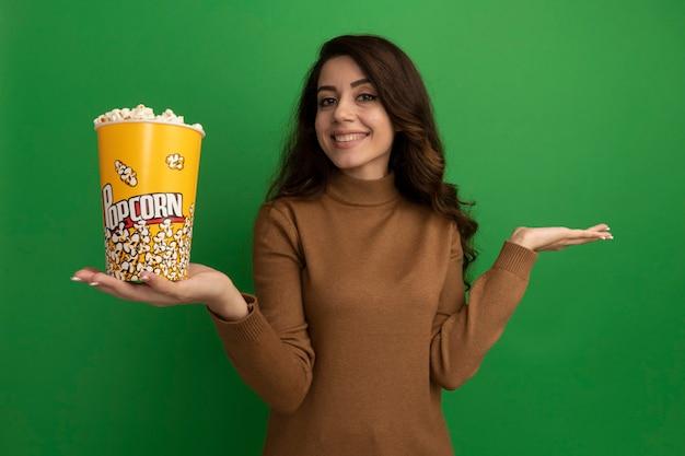 De glimlachende jonge mooie emmer van de meisjesholding popcorn en het spreiden van hand die op groene muur wordt geïsoleerd