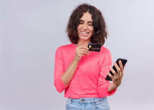 De glimlachende jonge mooie kaart van de vrouwenholding en mobiele telefoon op geïsoleerde witte muur met exemplaarruimte
