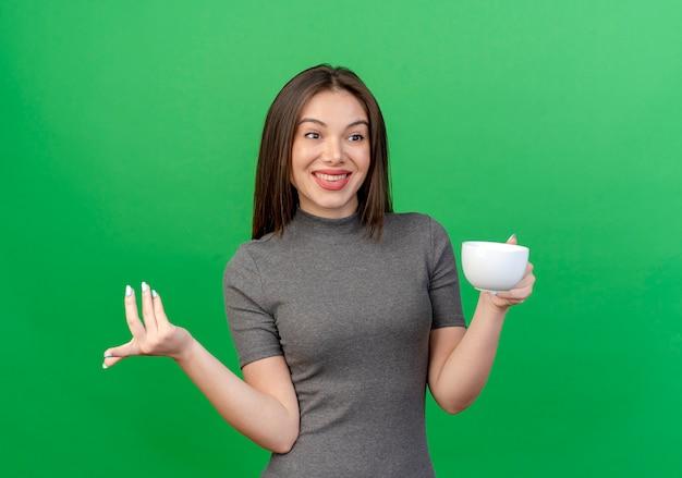 De glimlachende jonge mooie kop die van de vrouwenholding recht kijkt en hand in lucht houdt die op groene achtergrond wordt geïsoleerd