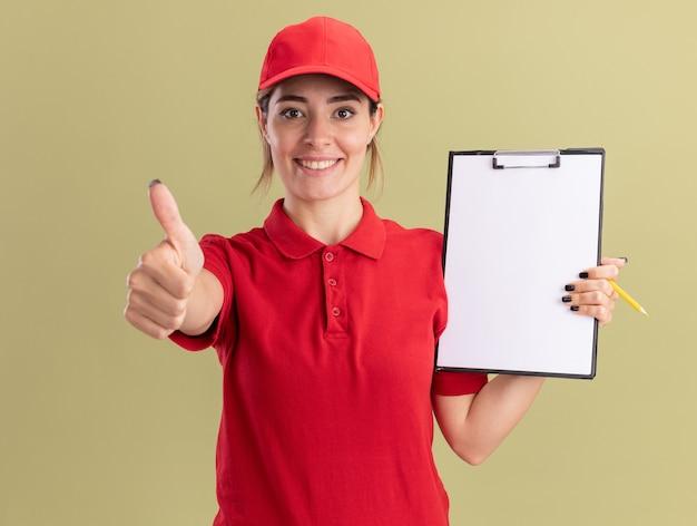 De glimlachende jonge mooie leveringsvrouw in eenvormig beduimelt omhoog en houdt klembord dat op olijfgroene muur wordt geïsoleerd