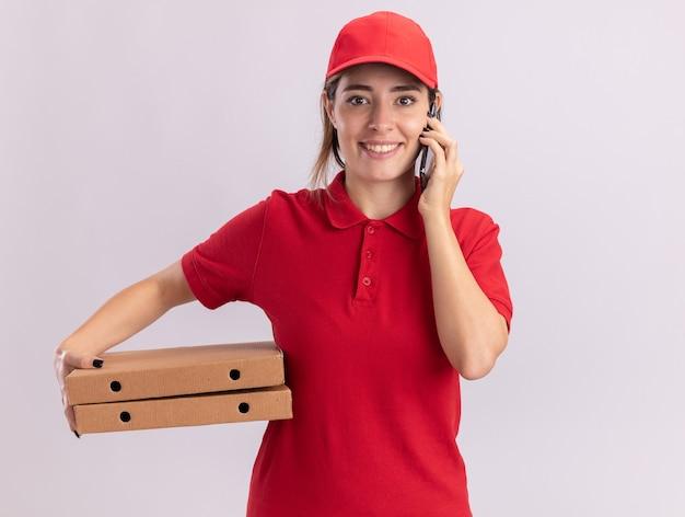 De glimlachende jonge mooie leveringsvrouw in eenvormige besprekingen over telefoon en houdt pizzadozen die op witte muur worden geïsoleerd