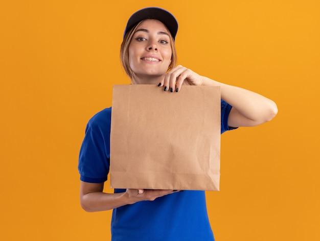 De glimlachende jonge mooie leveringsvrouw in uniform houdt document pakket dat op oranje muur wordt geïsoleerd