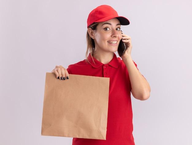De glimlachende jonge mooie leveringsvrouw in uniform houdt document pakket en spreekt over telefoon die op witte muur wordt geïsoleerd
