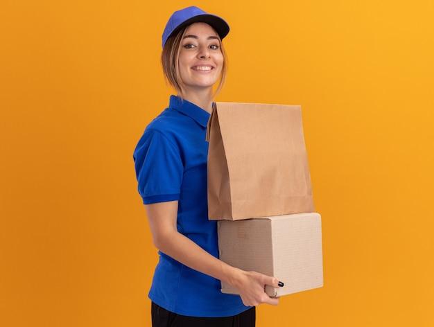 De glimlachende jonge mooie leveringsvrouw in uniform houdt document pakket op kartondoos die op oranje muur wordt geïsoleerd