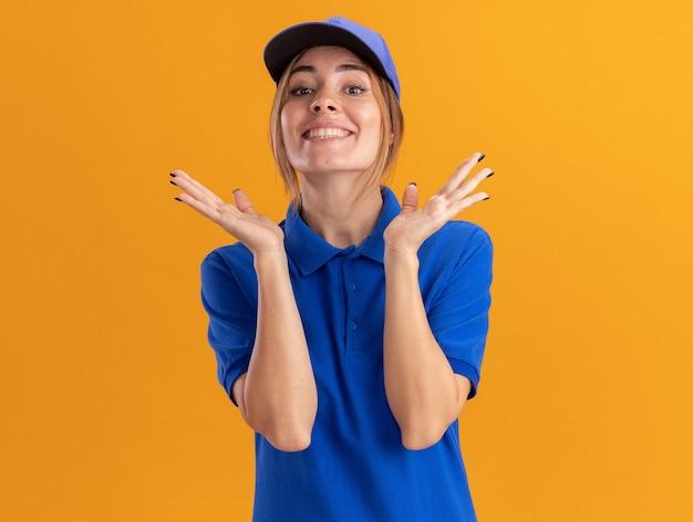 De glimlachende jonge mooie leveringsvrouw in uniform houdt handen open geïsoleerd op oranje muur