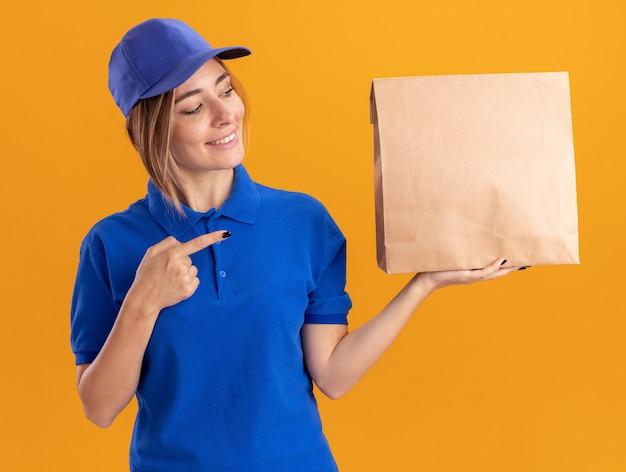 De glimlachende jonge mooie leveringsvrouw in uniform kijkt en wijst op document pakket dat op oranje muur wordt geïsoleerd
