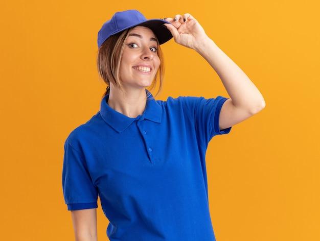 De glimlachende jonge mooie leveringsvrouw in uniform legt hand op glb dat op oranje muur wordt geïsoleerd