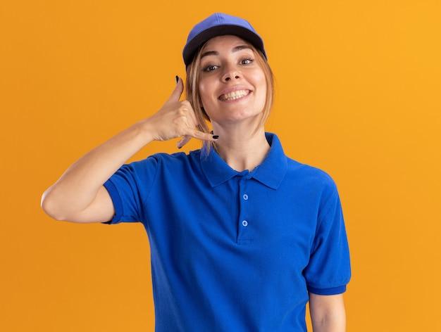 De glimlachende jonge mooie leveringsvrouw in uniforme gebaren noemt me handteken dat op oranje muur wordt geïsoleerd