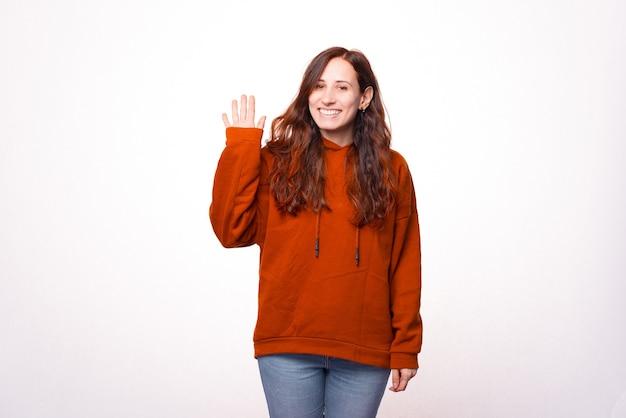 De glimlachende jonge mooie vrouw toont hallo gebaar en bekijkt de camera