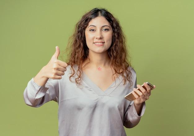 De glimlachende jonge mooie vrouwelijke telefoon van de beambteholding haar duim omhoog geïsoleerd op olijfgroene muur