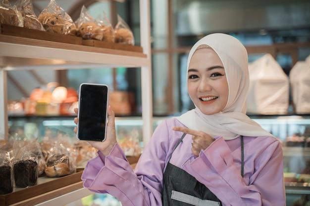 De glimlachende jonge moslimvrouw met hijab toont het scherm van haar gsm aan camera