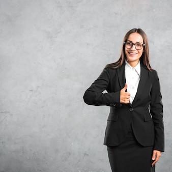 De glimlachende jonge onderneemster die duim toont ondertekent omhoog tegen concrete achtergrond