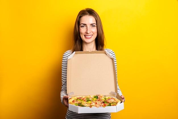 De glimlachende jonge pizza van de vrouwenholding in verpakking op geel.