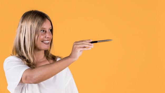 De glimlachende jonge schakelt vrouw het tonen van het voorstellen gesturing met holdingspen uit over heldere achtergrond
