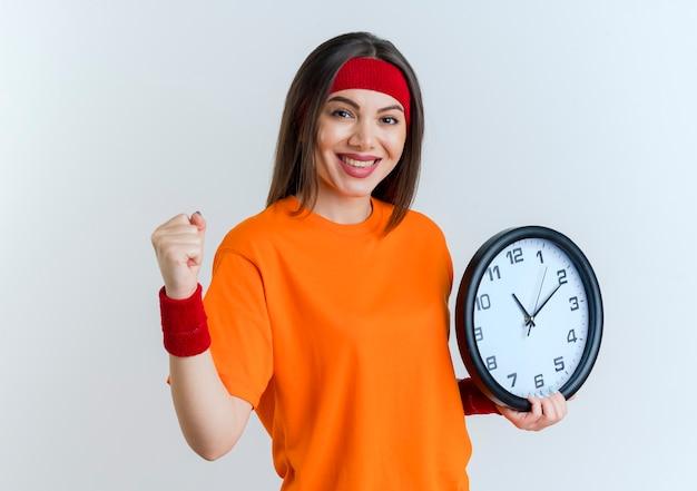 De glimlachende jonge sportieve vrouw die hoofdband en polsbandjes draagt die klok doen is sterk gebaar dat op witte muur wordt geïsoleerd