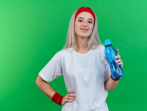 De glimlachende jonge sportieve vrouw met bretels die hoofdband en polsbandjes dragen houdt waterfles en legt hand op taille die op groene muur wordt geïsoleerd