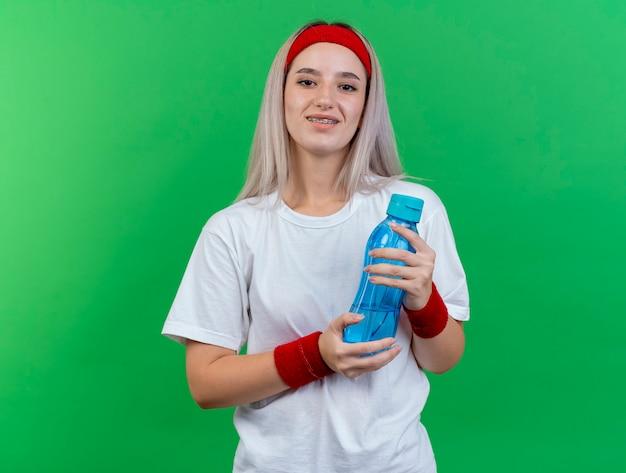 De glimlachende jonge sportieve vrouw met steunen die hoofdband en polsbandjes dragen houdt waterfles die op groene muur wordt geïsoleerd