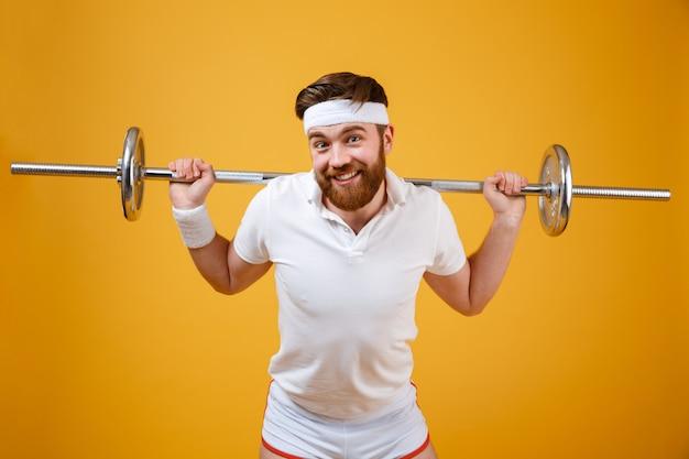 De glimlachende jonge sportman maakt sportoefeningen met barbell