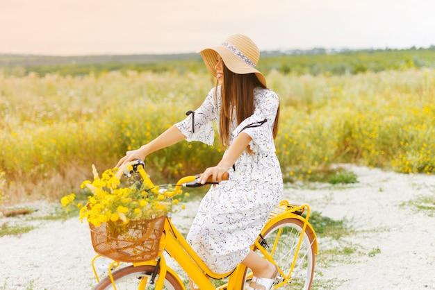 De glimlachende jonge vrouw berijdt haar gele fiets op een gebied