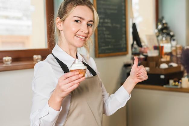 De glimlachende jonge vrouw die gebakken muffins houdt in hand tonend duim ondertekent omhoog