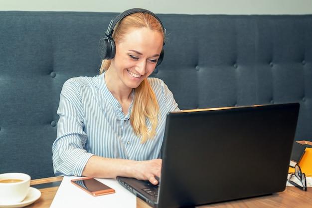 De glimlachende jonge vrouw die hoofdtelefoons draagt zit voor open laptop bij een lijst bij koffie.