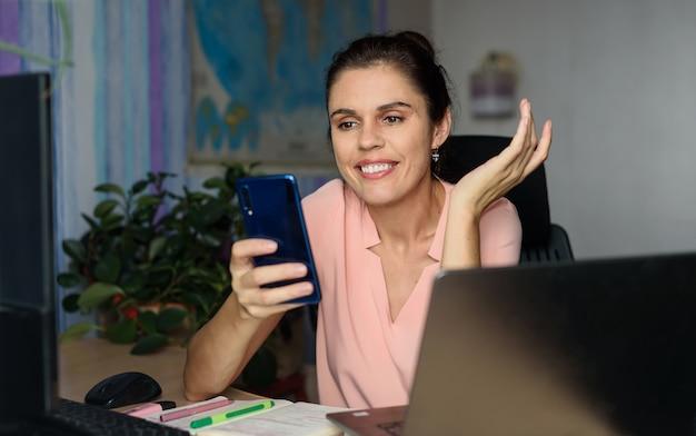 De glimlachende jonge vrouw die naar huis dichtbij laptop werken, zijdelings schouderophalend, houdt telefoon, glimlach zeggend droevig kan niet met videogesprek helpen. wereldkaart op de achtergrond