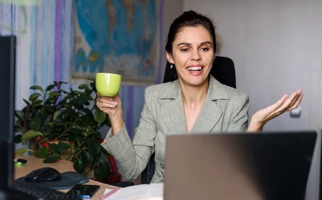 De glimlachende jonge vrouw die naar huis dichtbij laptop werkt, zijwaarts met handen ophaalt, glimlach die sorry zegt kan niet helpen en kijkt aan laptop. wereldkaart op de achtergrond