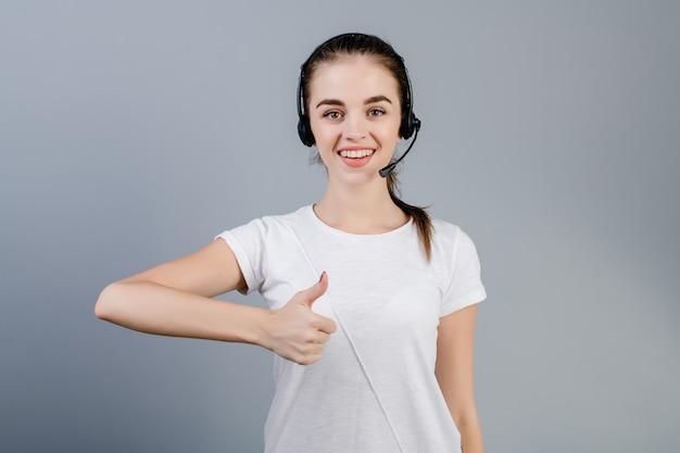 De glimlachende jonge vrouw die van de call centreverzender hoofdtelefoon dragen die klanten beantwoorden die duimen tonen die omhoog over grijs worden geïsoleerd