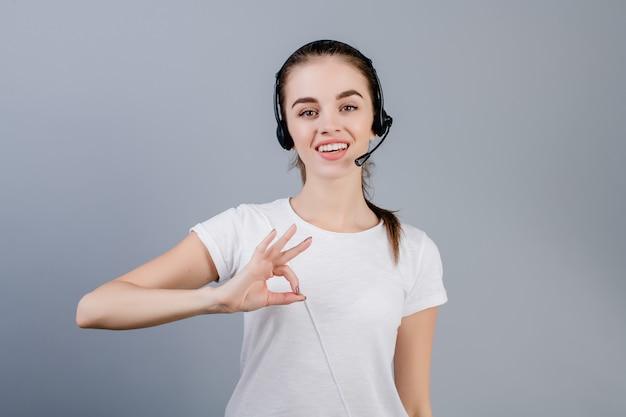 De glimlachende jonge vrouw die van de call centreverzender hoofdtelefoon dragen die klanten beantwoorden die ok gebaar tonen dat over grijs wordt geïsoleerd