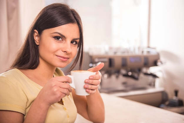 De glimlachende jonge vrouw drinkt koffie.