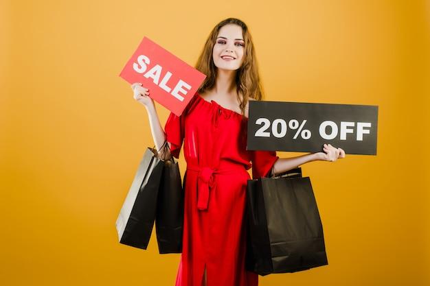 De glimlachende jonge vrouw heeft verkoop 20% van teken met kleurrijke die het winkelen zakken over geel wordt geïsoleerd