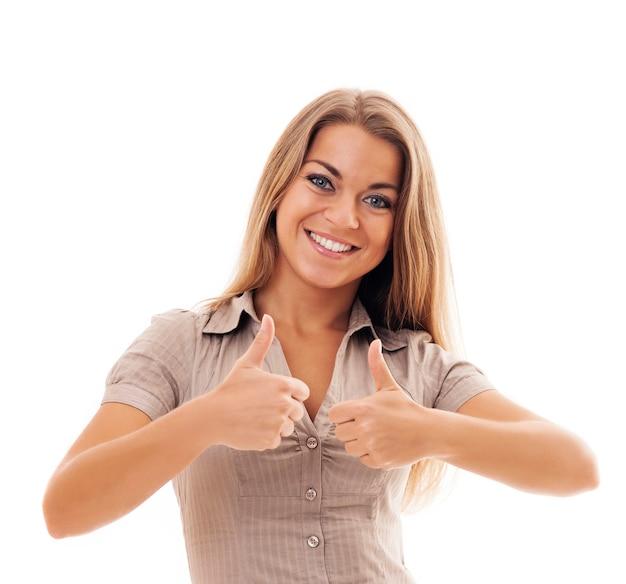 De glimlachende jonge vrouw heft duimen op