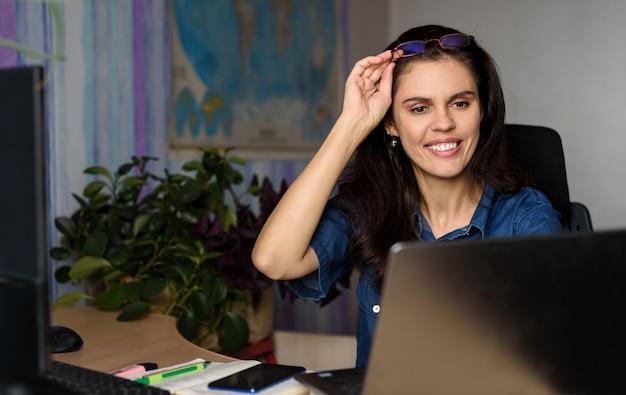 De glimlachende jonge vrouw in denimoverhemd werkt online met laptop