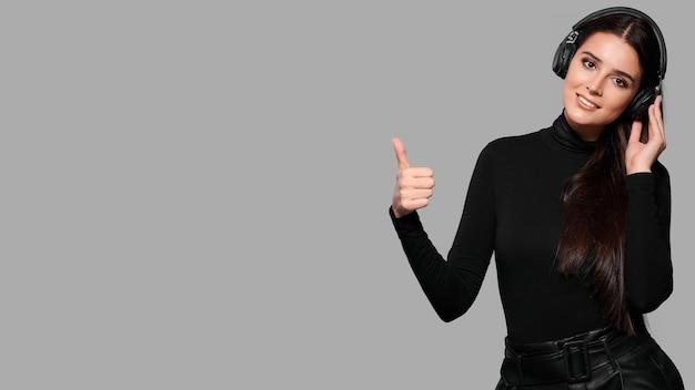 De glimlachende jonge vrouw in draadloze hoofdtelefoons toont duim omhoog gebaar, het wijfje luistert naar muziek, geïsoleerde achtergrond