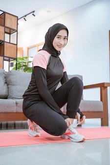 De glimlachende jonge vrouw in een hijab-workoutoutfit hurkt neer terwijl ze haar schoenveters vastmaakt voordat ze binnenshuis traint