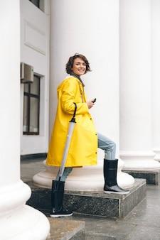 De glimlachende jonge vrouw kleedde zich in regenjas