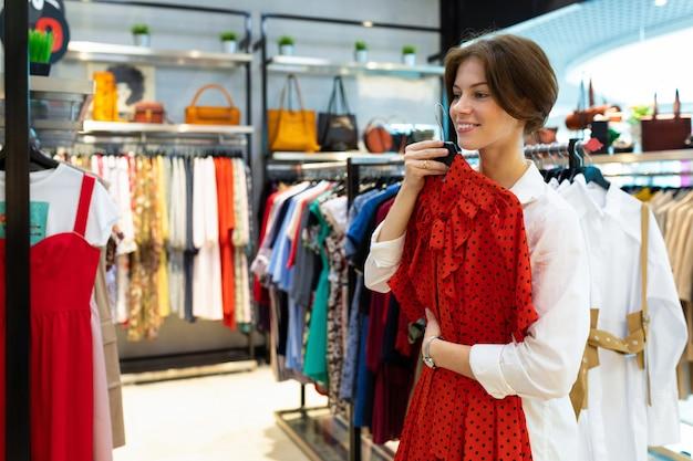 De glimlachende jonge vrouw koos een rode kleding voor het winkelen met korting in een modeboetiek
