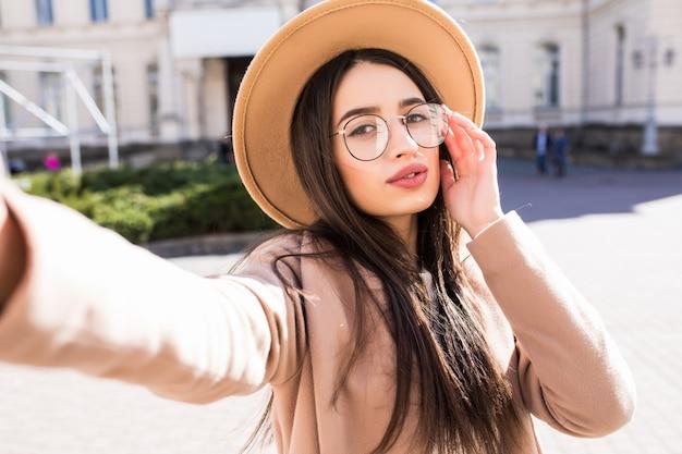 De glimlachende jonge vrouw maakt selfie in openlucht op haar nieuwe smartphone in de stad in zonnige dag