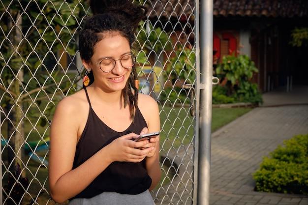De glimlachende jonge vrouw met dreadlocks schrijft een sms-bericht op haar mobiel.
