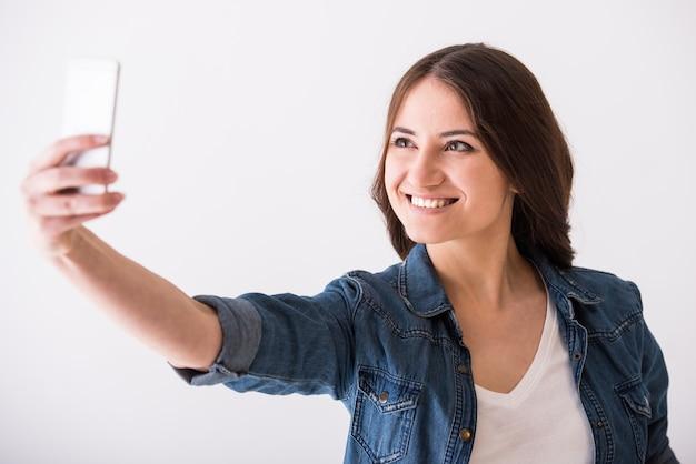 De glimlachende jonge vrouw neemt selfie foto.