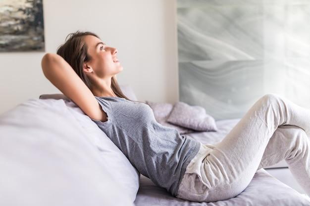 De glimlachende jonge vrouw ontspant liggend op laag