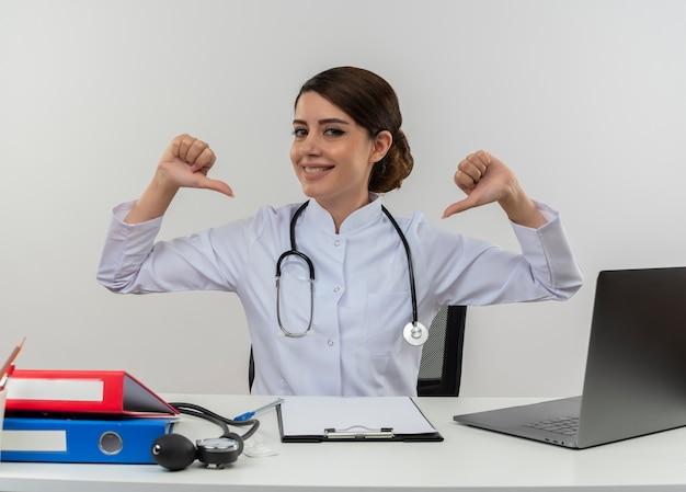 De glimlachende jonge vrouwelijke arts die medische mantel met stethoscoop draagt die aan bureauwerk op computer met medische hulpmiddelen zit, wijst naar zichzelf met exemplaarruimte